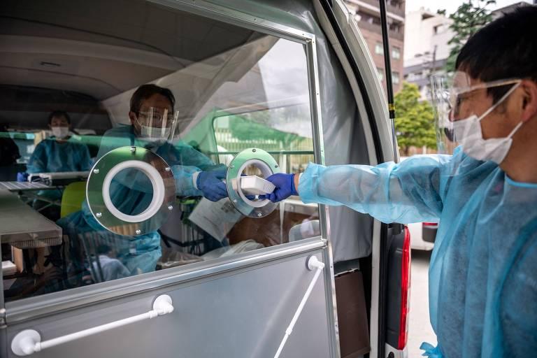 Técnico de saúde pega amostra para teste de detecção de Covid-19 de outro técnico de saúde. Amostra passa por uma pequena abertura em veículo. Os dois estão protegidos por máscara e face shield
