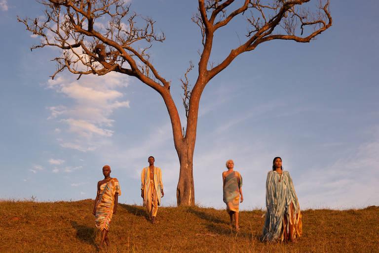 Quatro modelos posam ao lado de uma árvore seca