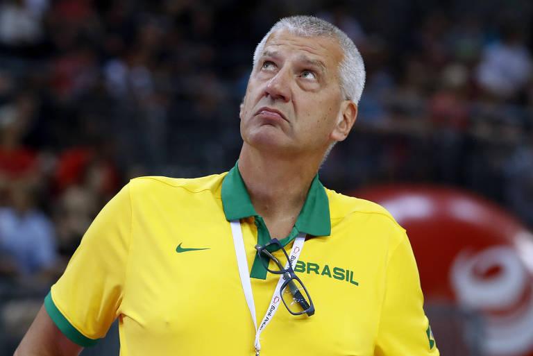 Petrovic, com blusa polo amarela e verde, olha para cima