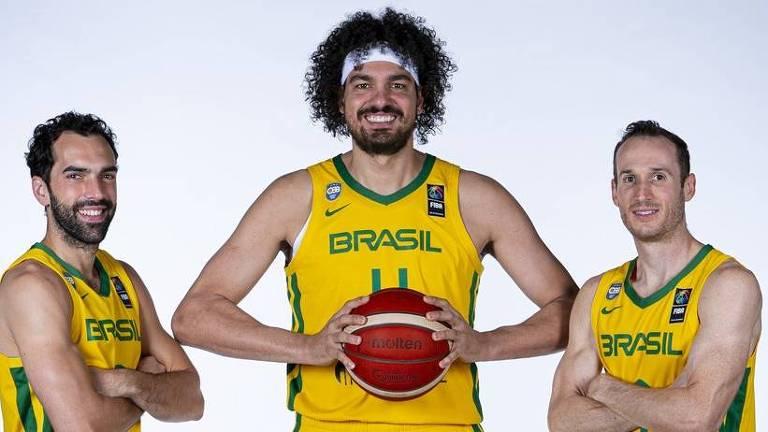 Jogadores posam com uniforme da seleção; ao centro, Varejão segura uma bola de basquete