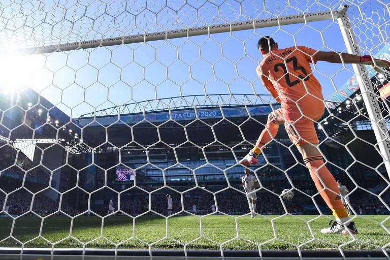 Unai Simón vai buscar a bola na rede após o gol contra bizarro da Espanha que abriu o placar