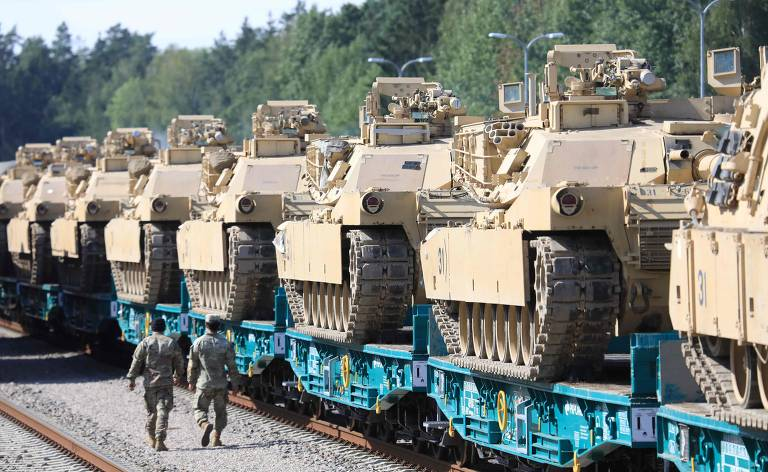 Tanques bege enfileirados em trem de carga de base azul. Dois militares de uniforme bege camuflado caminham ao lado dos tanques