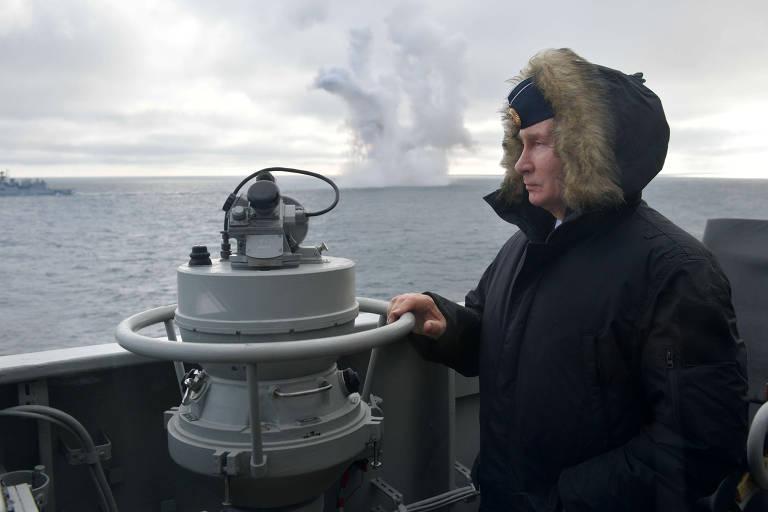 No canto direito, Putin observa o mar de pé vestido em um casaco azul-marinho com pele no capuz e uma boina azul-marinho. Ele apoia sua mão direita no barco. Ao fundo, o mar e uma nuvem de fumaça. Céu nublado.