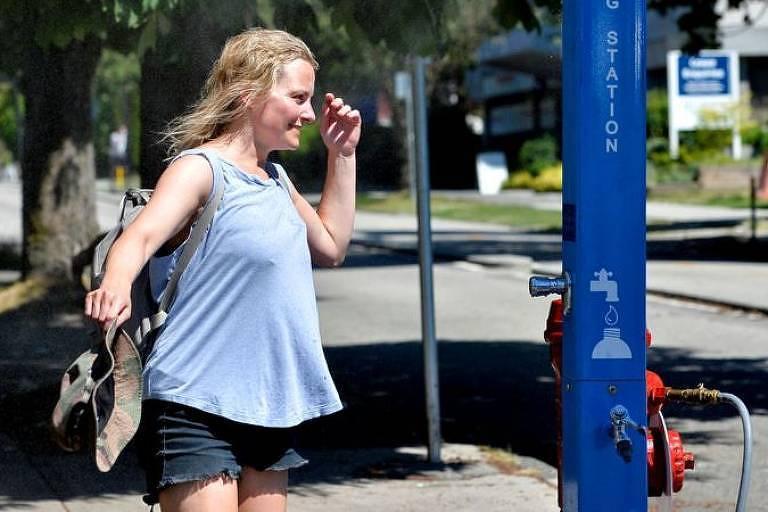 Mulher ao lado de estação de água para refrescar pedestres