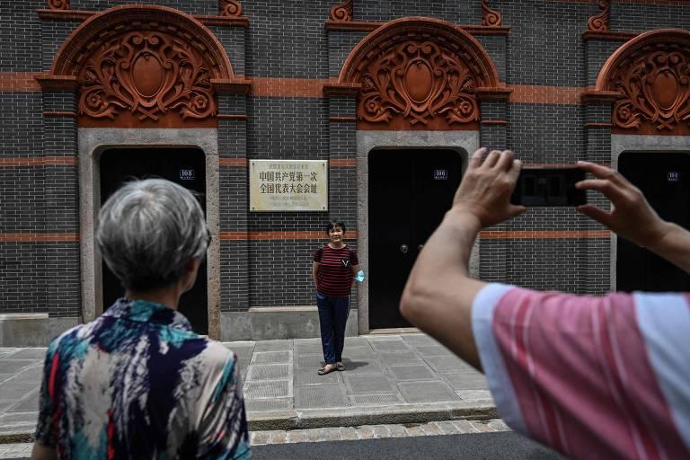 Mulher posa para foto em frente ao museu do primeiro Congresso do Partido Comunista Chinês, em Xangai
