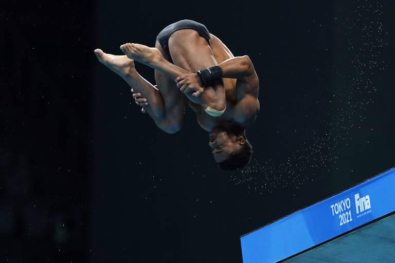 Atleta de cabeça para baixo e segurando as pernas durante o salto