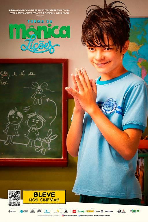 Menino branco de camiseta azul em uma sala de aula