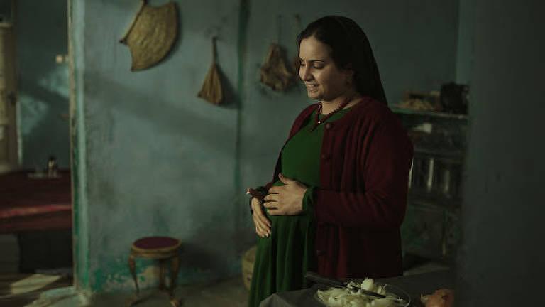 Mulher grávida acaricia a barriga