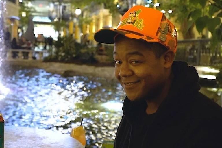 Homem negro com boné laranja e moletom preto sentado em uma fonte