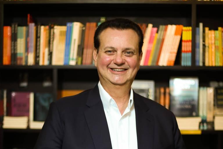 Foto mostra o presidente do PSD, Gilberto Kassab, posando sorridente de paletó e sem gravata na frente da estante cheia de livros numa livraria de São Paulo