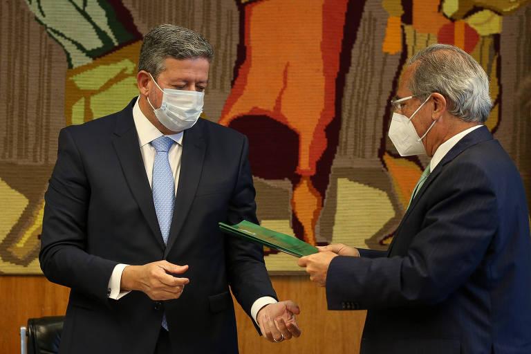 Arthur Lira, presidente da Câmara dos Deputados, de pé, recebe pasta com a reforma tributária das mãos do ministro Paulo Guedes, de pé ao lado dele, segurando o documento