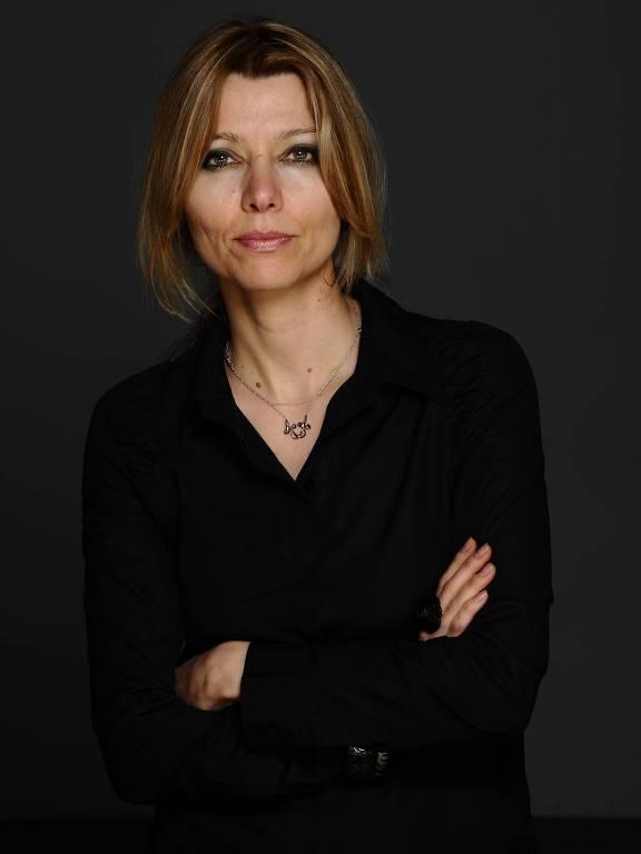 mulher branca de braços cruzados usando camisa preta; ela tem cabelos claros e olhos claros e usa maquiagem forte em torno deles