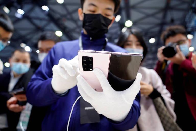 Funcionário manuseia celular da Huawei durante feira de tecnologia em Xangai