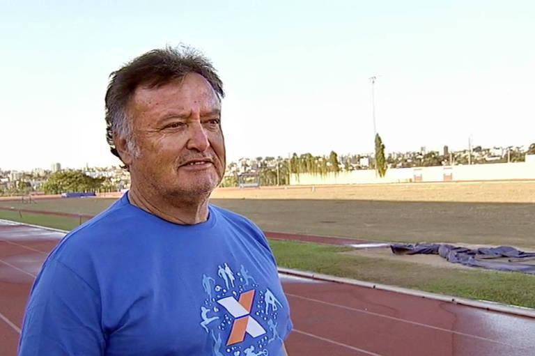 O técnico Luiz Alberto de Oliveira posa em frente a uma pista de atletismo