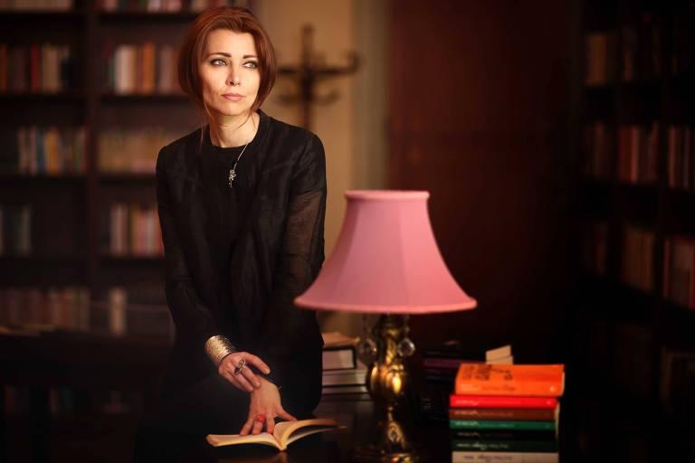 mulher em biblioteca encostada na mesa onde há livros e um abajur rosa. ela é branca e usa uma blusa de manga comprida preta