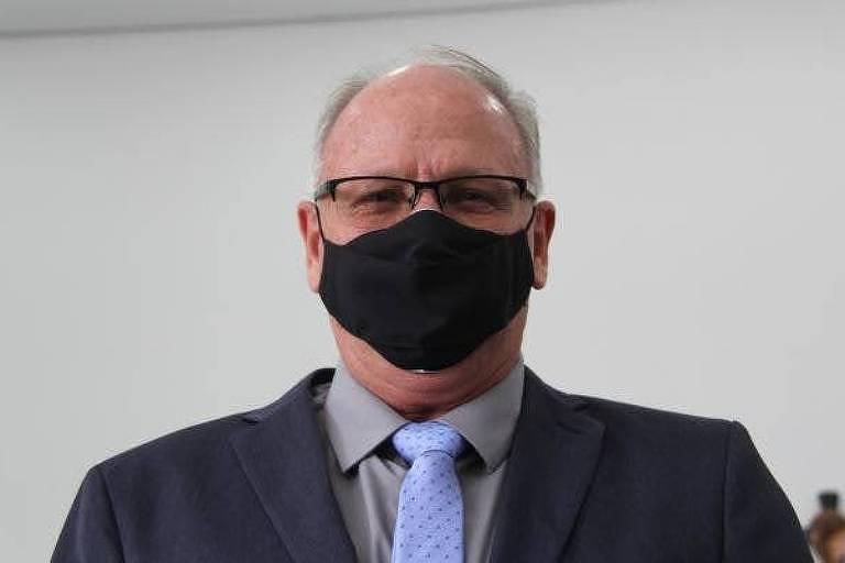 Marcos Henrique Chiaradia (PSL) aparece de máscara. Ele usa terno e gravata e possui cabelos brancos
