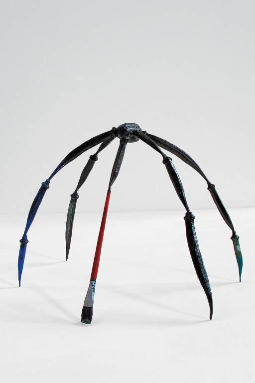 Escultura de uma aranha cujas patas são formadas por quiabos e um pincel
