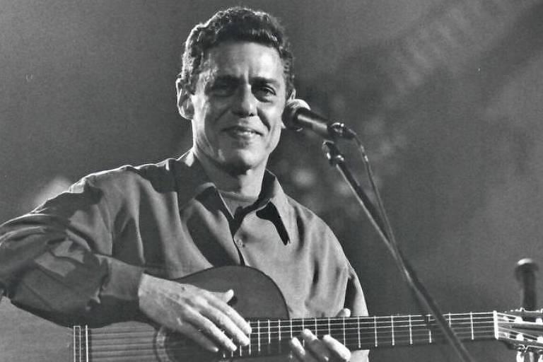 Homem branco tocando violão e sorrindo em foto preto e branco