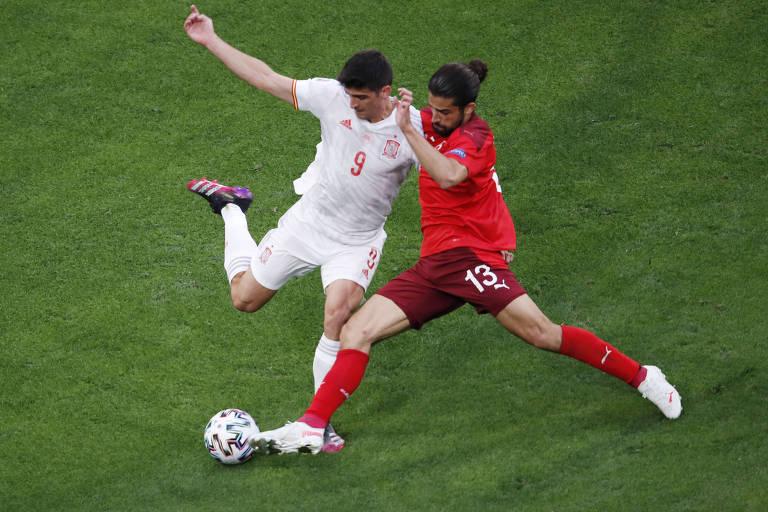 Jogador da Suíça trava jogador espanhol, como descrito no texto