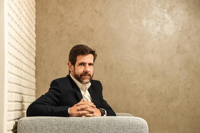 Homem de terno, sentado em poltrona cinza com os dedos entrelaçados, olhando para a câmera
