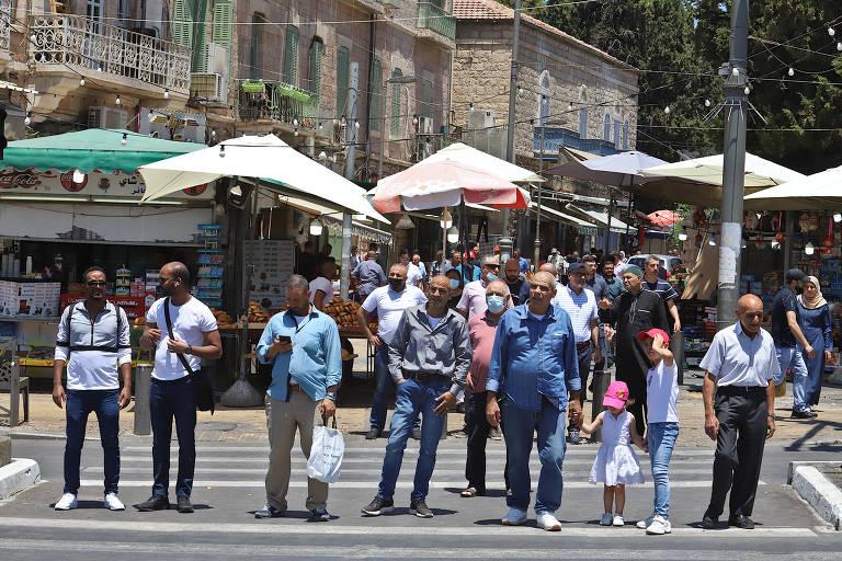 Dezenas de pessoas esperam para atravessar uma rua