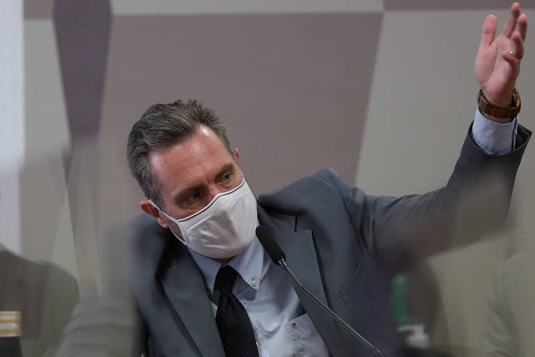 Homem de máscara terno e gravata levanta a mão ao falar em microfone