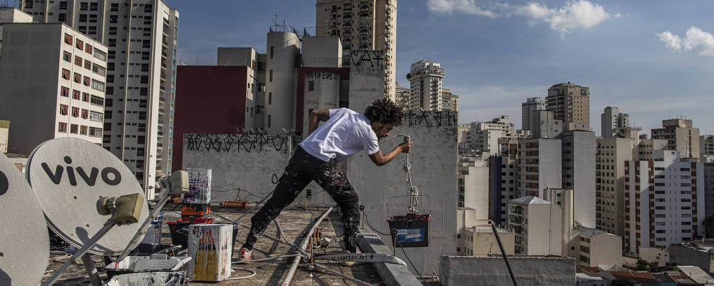 Kleber Pagu, em cima de um prédio de São Paulo, enquanto pinta um novo grafite