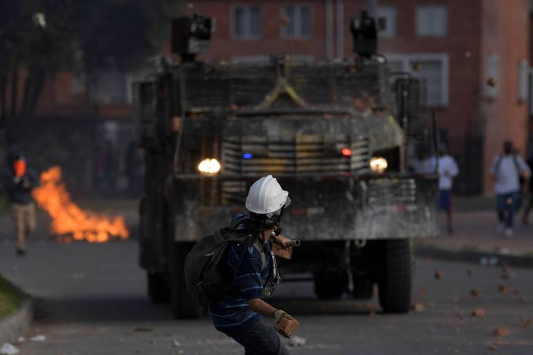 Manifestante lança pedaço de tijolo contra as forças de segurança no bairro de Suba, em Bogotá