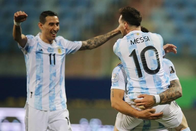 Lautaro Martinez levanta Messi após receber passe do camisa 10 para marcar o segundo gol da Argentina; eles são observados por Di Maria