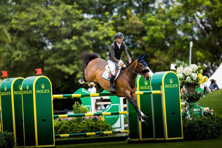 Cavaleiro montado em cavalo salta sobre obstáculo
