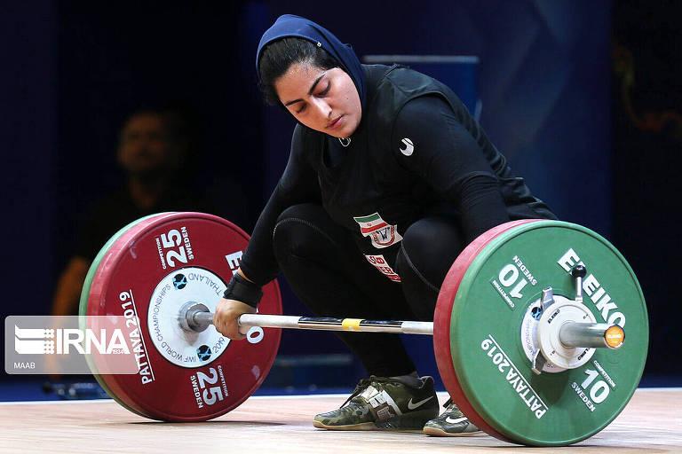 A levantgadora de peso Parisa Jahanfekrian se agacha para tentar levantar peso durante competição. Ela usa vestimentas que cobrem todo o corpo, com exceção do rosto e das mãos