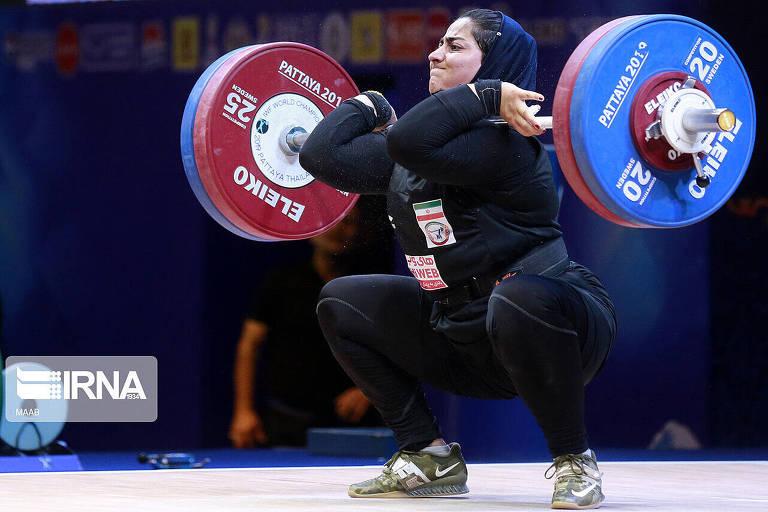 Parisa Jahanfekrian aparece agachada levantando peso durante Campeonato Mundial, na Tailândia. Ela está com roupa preta que cobre todo o corpo, exceto as mãos e o rosto