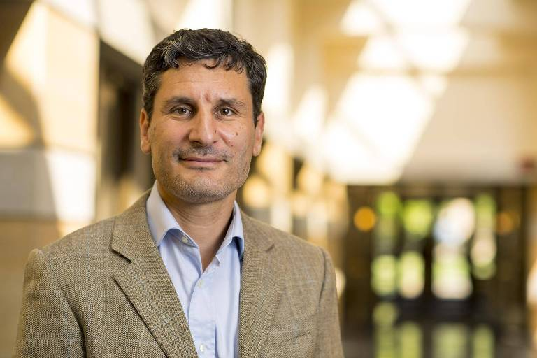 O professor Diego Sánchez-Ancochea, economista da Universidade de Oxford, sorrindo, usando roupa social posa para foto em um salão iluminado