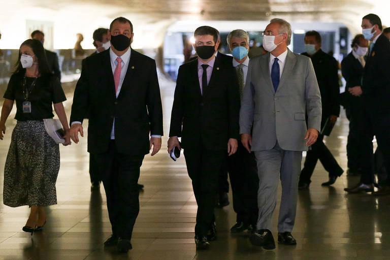 Os três homens são brancos e vestem ternos e usam máscaras. Estão caminhando lado a lado, e há outras pessoas ao fundo