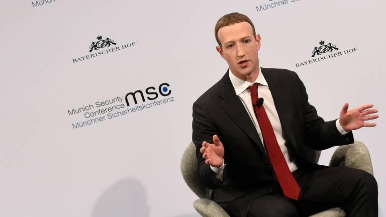 Homem de terno preto e gravata vermelha, sentado, movimenta as mãos enquanto fala