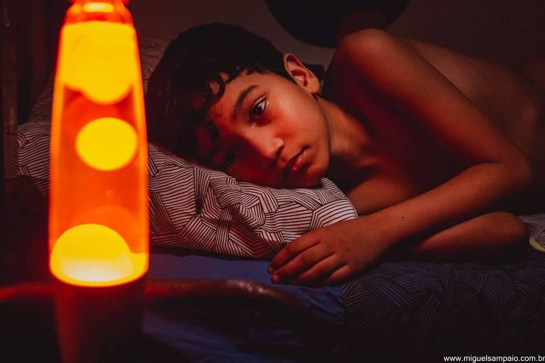 menino olha para lamparina