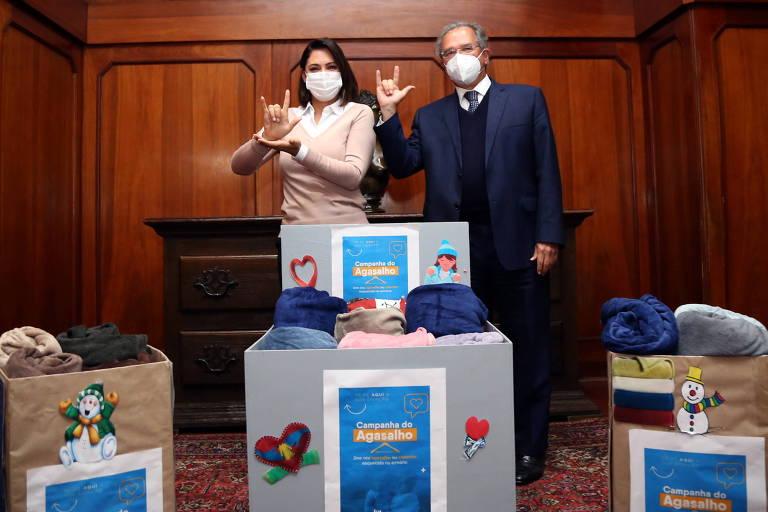 Paulo Guedes e Michelle Bolsonaro, junto a doações da campanha de agasalhos, fazem sinal de 'eu te amo' em libras