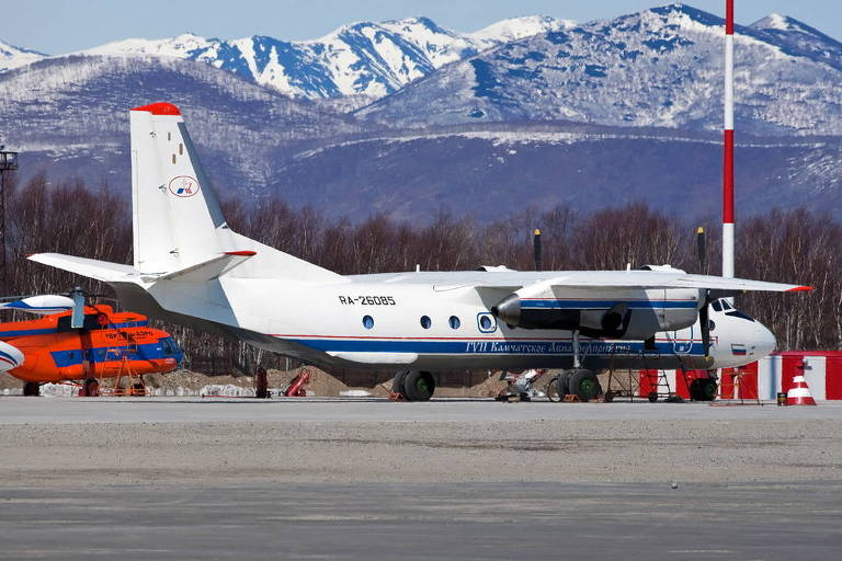 Avião branco em aeroporto frente a montanhas