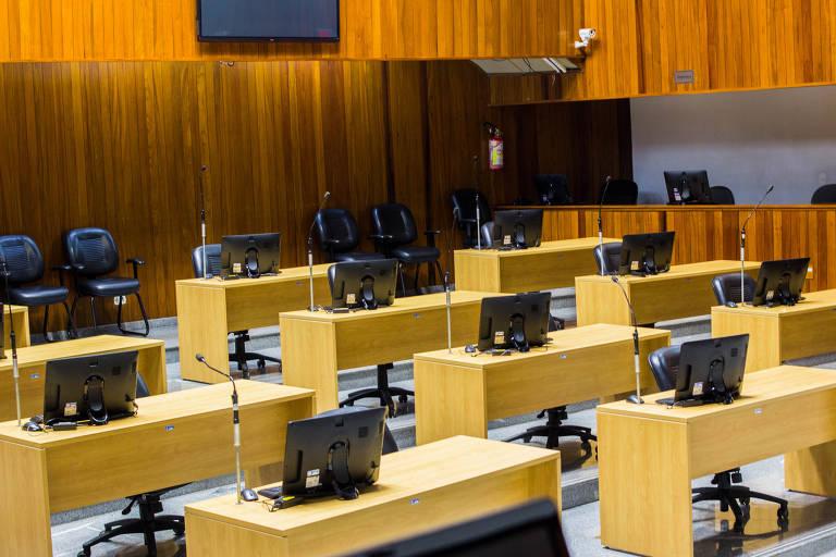 Imagem mostra mesas e computadores em uma sala que está vazia