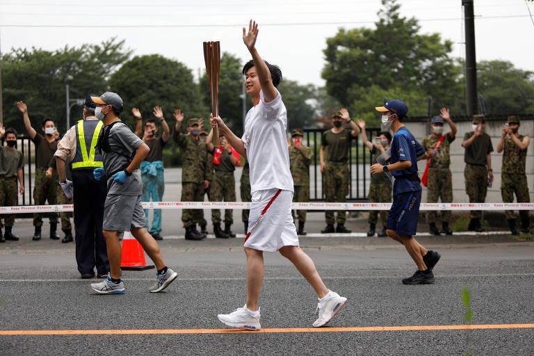 Corredor portando a tocha olímpica passa por rua de Saitama, no Japão. Forças policiais correm ao lado dele para fazer a segurança do símbolo olímpico