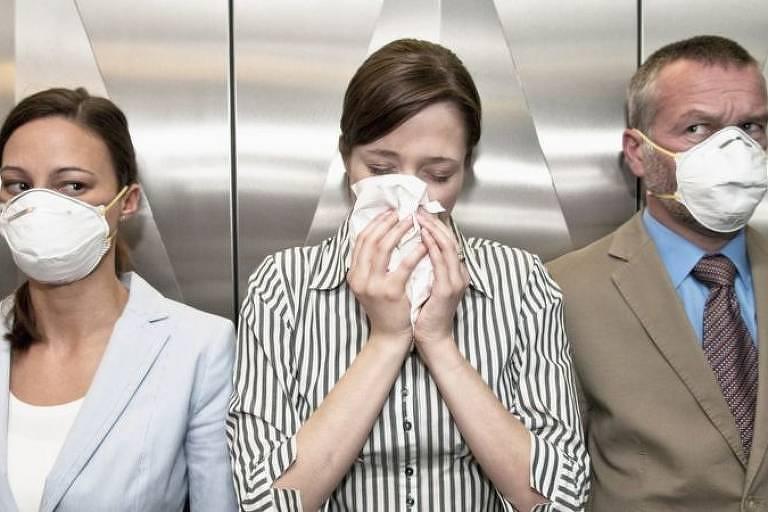 Imagem em primeiro plano mostra três pessoas. À esquerda, uma mulher de máscara, ao centro, outra mulher assoando o nariz com um lenço branco e, à esquerda, um homem de máscara