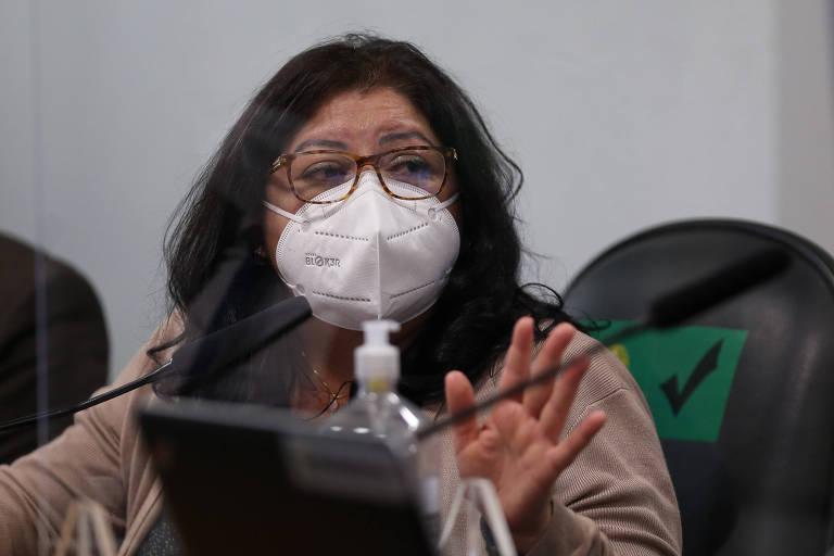 Uma mulher de óculos e máscara, gesticulando à mesa. Diante dela, uma tela de um notebook e um vidro de álcool em gel