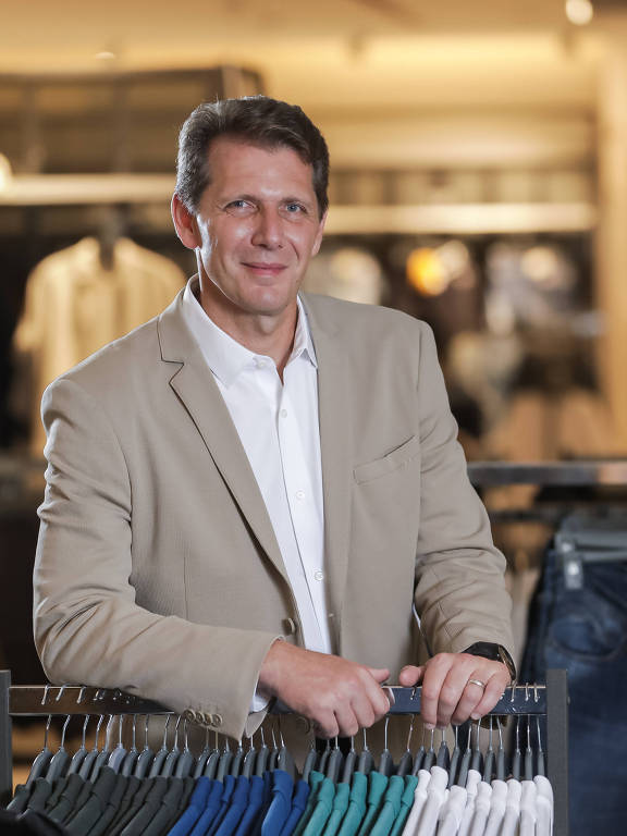 homem alto branco se apoia em arara de roupas em loja