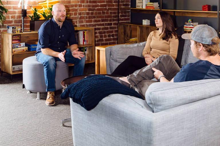 Três pessoas conversam sentadas