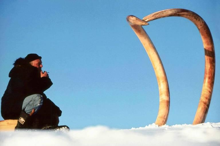 Pesquisador francês Bernard Buigues ao lado de presas de mamute escavadas na Sibéria