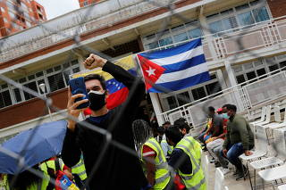 A man rises his fist in front of Cuban and Venezuelan flags at a vaccination center where Cuba's Abdala vaccine is being administered, in Caracas