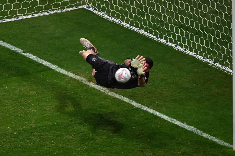 Emiliano Martinez salta para fazer a defesa na disputa de pênaltis contra a Colômbia