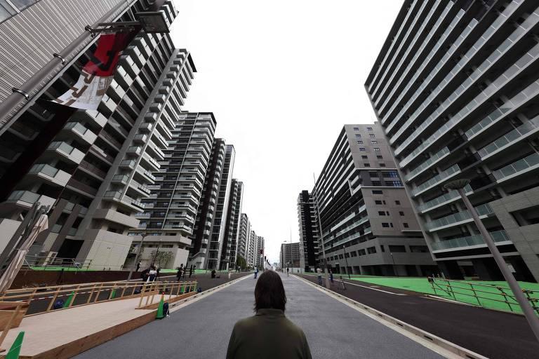 Homem no meio da rua observa prédios residenciais dos dois lados na Vila Olímpica que será usada nos Jogos Olímpicos e Paraolímpicos de Tóquio-2020
