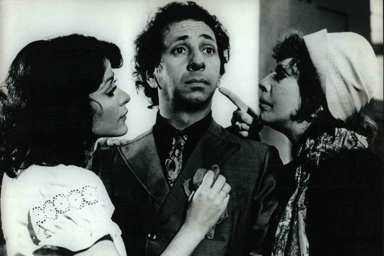 Homem ao meio de duas mulheres que estão próximas de suas bochechas