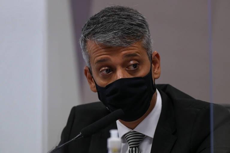 Um homem de máscara preta e terno diante de um microfone de mesa